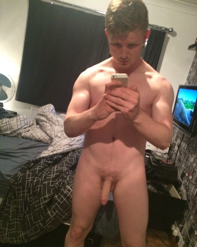 nude guy taking self pic in the mirror
